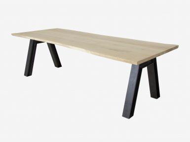 Industriele eettafel op maat genaamd Vos. Een stalen V-poot met een boomstam tafelblad van eikenhout.